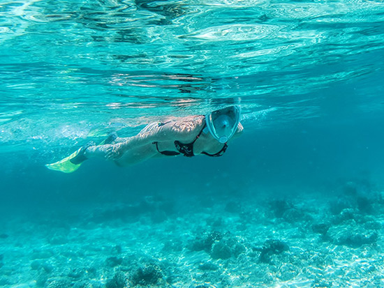 Female snorkeling in clear blue water