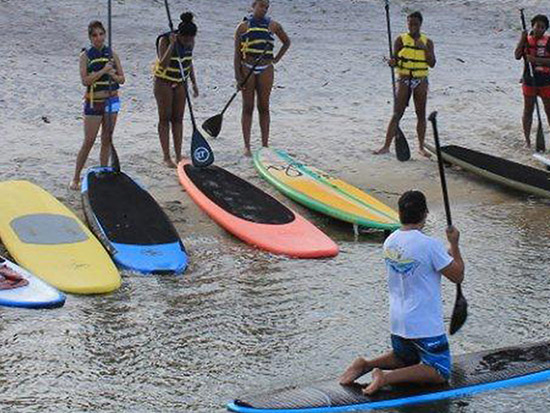 Instructor teach a group about paddle boarding