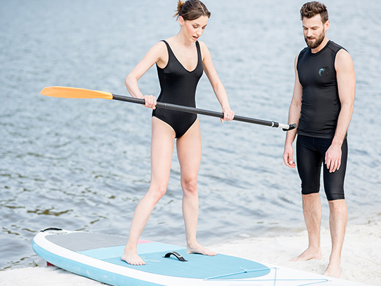 Woman learning to paddle board