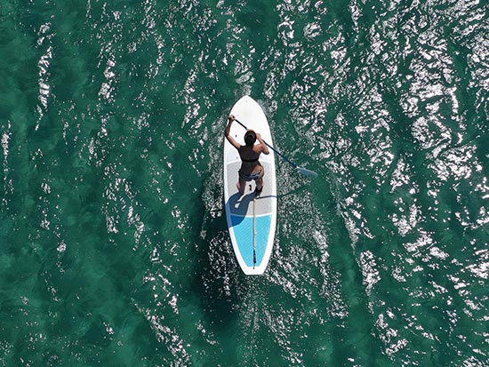 Aerial view of girl paddle boarding