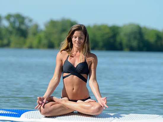 Girl in black bikini doing yoga on paddle board