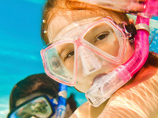 Young girl in pink snorkel gear