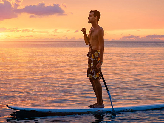 Guy paddle boarding at sunrise